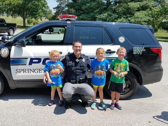 Officer Cory Landis of the Springettsbury Township Police Department entertained, from left, 4-year-old Evelyn Pittman, 6-year-old Marie Pittman and 6-year-old Lucas Buckler on Saturday afternoon at Springettsbury Township Park.