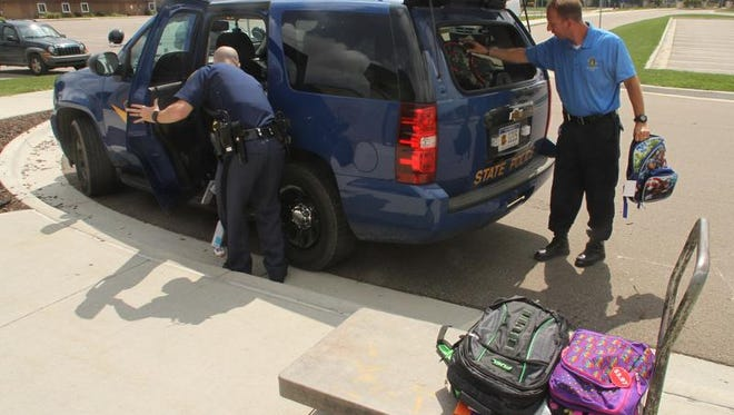 Michigan State Police Troopers Andrew Knapp, right, and Brian Alexander unload school supplies from a stuffed sport utility vehicle as they deliver backpacks and related materials to the Livingston Educational Service Agency in Howell. The materials were given to students in need.