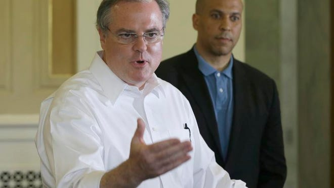 U.S. Sen. Mark Pryor, D-Ark., left, speaks during a news conference at the Arkansas state Capitol as U.S. Sen. Cory Booker, D-N.J., listens in Little Rock on Saturday. Booker accused Pryor's Republican rival, Tom Cotton, of going against a bipartisan tradition by opposing disaster aid for the states hit by Superstorm Sandy.