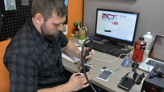 Josh Nelson, owner of LGS Electronics in St. Cloud, opens a Samsung Galaxy S5 to replace the screen Wednesday in his store. Nelson said heat, water and impact damage are the most common problems he sees in summer. If a phone gets wet, the best thing to do is bring it in right away so it can be disassembled and dried. Don't put it in a bag of rice to dry it, Nelson said.