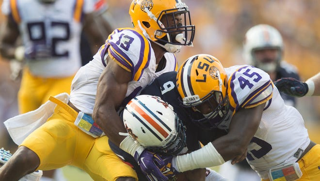 Louisiana State defensive back Dwayne Thomas (13) and Louisiana State linebacker Deion Jones (45) tackles Auburn Tigers quarterback Jeremy Johnson (6) during the NCAA football game between LSU Tigers and Auburn on Saturday, Sept. 19, 2015, at Tiger Stadium in Baton Rouge, La. LSU Tigers defeated Auburn Tigers 45-21.Albert Cesare / Advertiser