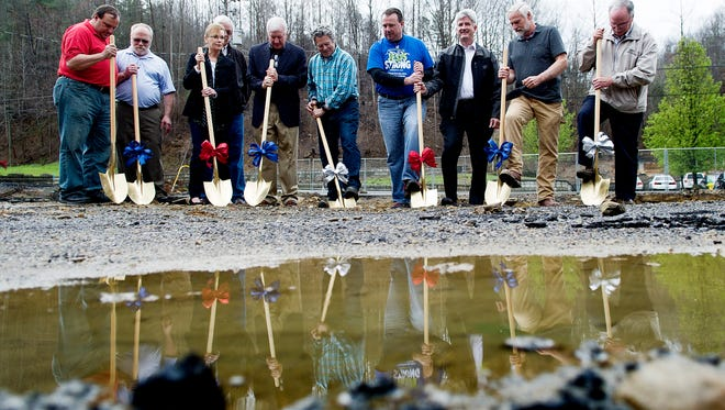 City officials and church members including Pastor Kim McCroskey, center, blue, break ground during the groundbreaking ceremony of the new Roaring Fork Baptist Church after the congregationlost its building in the Gatlinburg wildfires in November in Gatlinburg, Tennessee on Tuesday, March 28, 2017.