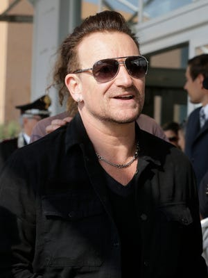 """FILE - In this Sept. 27, 2014 file photo, Bono smiles upon his arrival in Venice, Italy, to attend George Clooney's wedding ceremony. Bono says his ever-present sunglasses aren't a rock-star affectation — he has suffered from glaucoma for 20 years. told the BBC's """"Graham Norton Show"""" that he had the condition, but """"I have good treatments and I am going to be fine. (AP Photo/Luca Bruno, File)"""