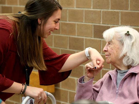 Molly MacLachlan, a recreational therapist at the Jewish Home of Rochester, talks with resident Joan Atvell during an art show for residents to browse works by local artists.