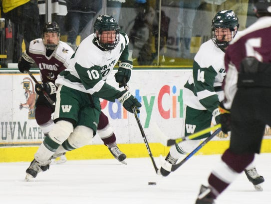 Woodstock's Steven Townley (10) skates with the puck