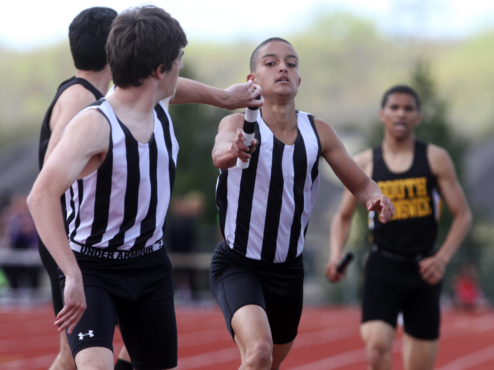 Scott Belton, right, of Old Bridge hands the baton to teammate Ed Zaleck during the 4x800 at the GMC Relays, Tuesday, April 28, 2015, in South Brunswick, NJ.