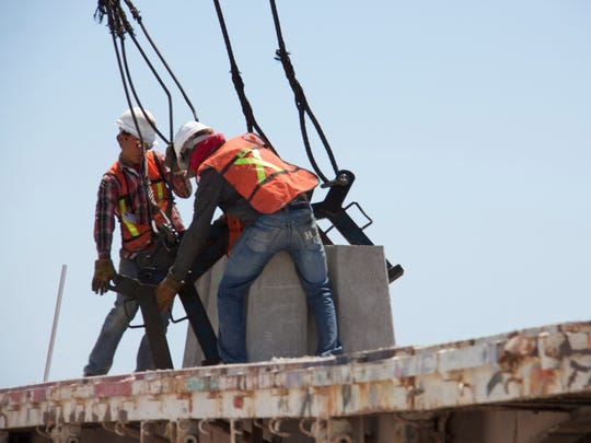 Workers unload a concrete block for the jetty. Those