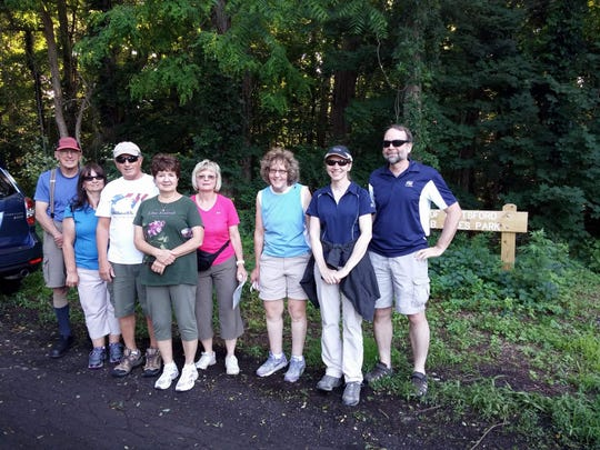 Walking group poses for a snapshot in front of the Janes Park sign on Roosevelt Road in East Rochester before starting out on a recent walk.