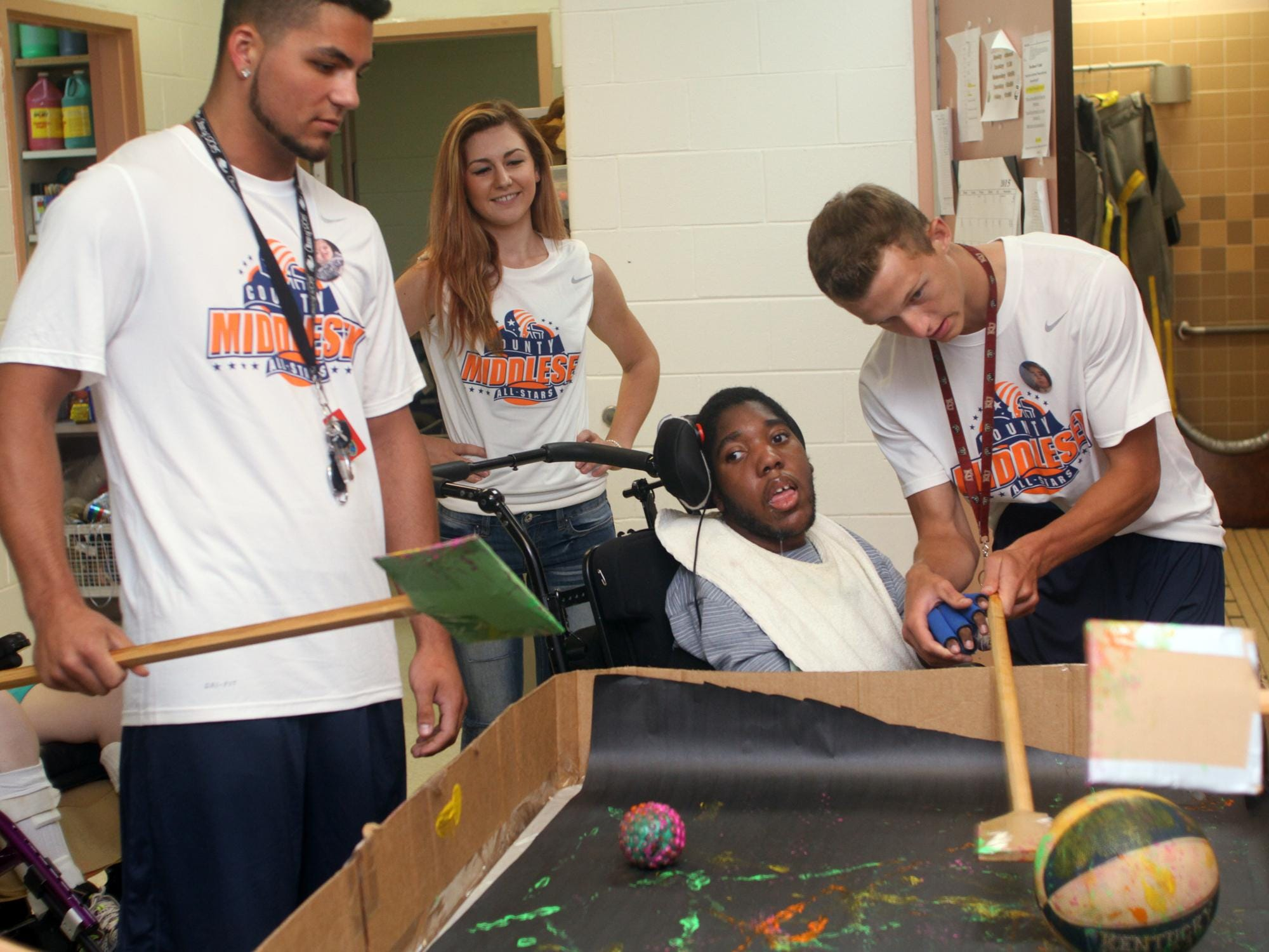 Snapple Bowl players Johnny Chillemi, left, and Tyler Valovcin, right, create artwork with Lakeview student Andrew (last name withheld), by rolling paint-covered balls during a visit to the Lakeview School in Edison on Monday. In the background is Snapple Bowl volunteer Adriana Kania.