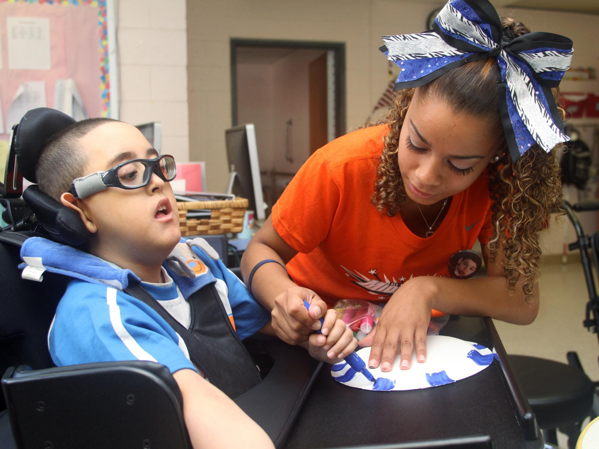 Cheerleader Amber Torres of Carteret decorates a noise maker with Justin (last name withheld) during a visit to the Lakeview School in Edison on Monday.