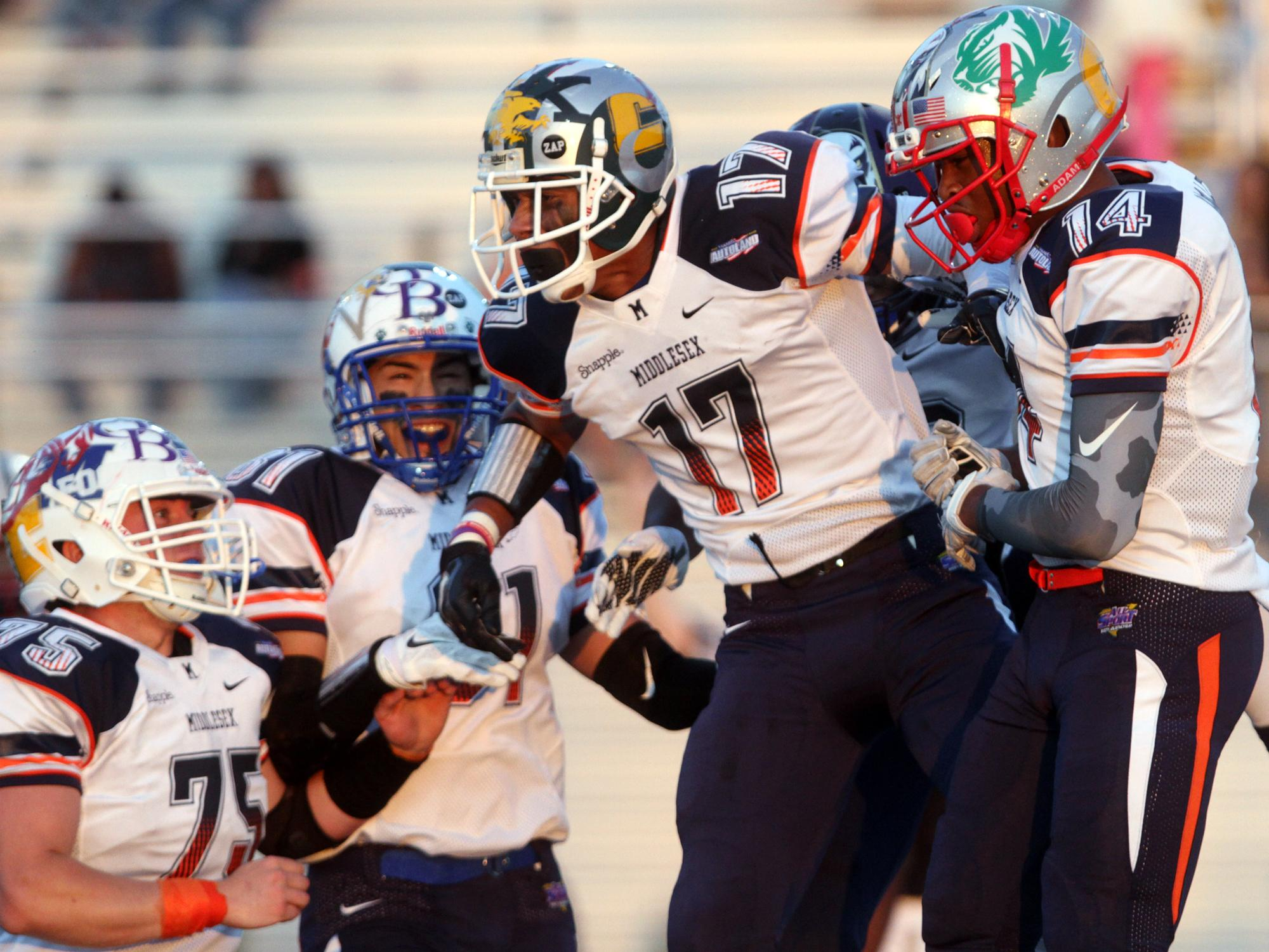 Javon Hicks (17) of St. Joseph celebrates with Middlesex teammates after scoring late in the second quarter during Snapple Bowl XXII, Thursday, July 16, 2015, at Kean University in Union, NJ.