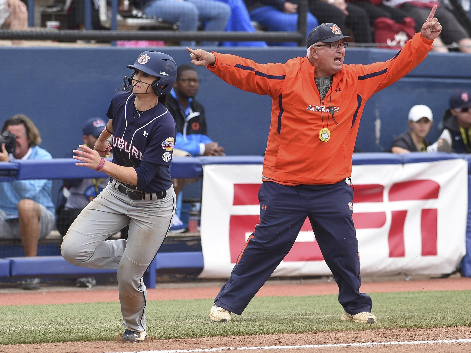 Coach Clint Myers waves Haley Fagan (2) around third in the 2015 NCAA Women's College World Series in Oklahoma City, Okla. on Saturday, May 30, 2015.