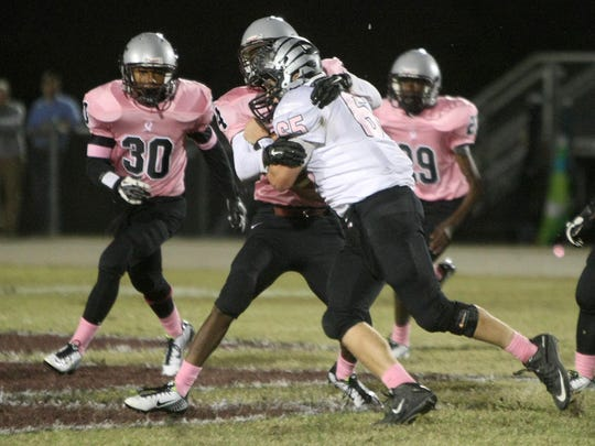 South Side's Jordan Taylor (65) collides with Liberty's Jonathan Bradford (4) at Liberty High School on Friday.