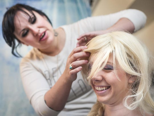 Whitney Graef, owner of Sweet Pea's Princess Rental and More, puts a Snow Queen wig on first-time volunteer Samantha Horton.