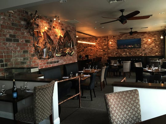 The interior of Feast restaurant features brick walls, images of the Truckee Meadows and a copper wall sculpture depicting a panoramic view of Reno.