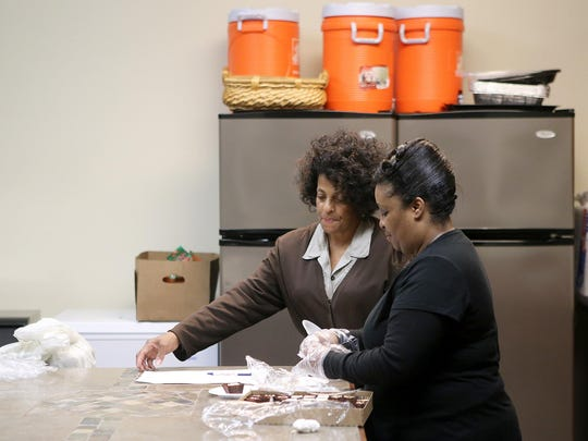 Ericil Cole, right, gets out more dessert at the New Life Christian Center on Nov. 19. Lorraine Ross is also pictured.