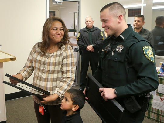 Maria Vela, left, and Madison County Deputy Dillon Wooley, right, react after receiving a set of commemorative pages from The Jackson Sun on Thursday at the Madison County Sheriff's Office. Maria Vela is Deputy Rosemary Vela's mother. Wooley was her fiancé. Also pictured is her brother Isaac Vela.