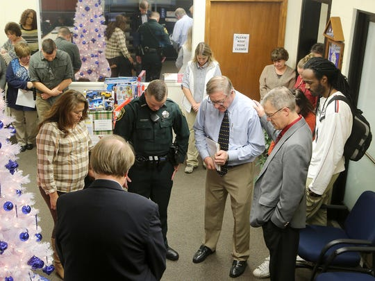 Colleagues, family and members of The Jackson Sun pray after presenting the family of Deputy Rosemary Vela with memorial gifts at the Madison County Sheriff's Office on Thursday.