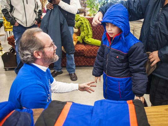 William Chafin, left, helps Tony Lavender, 7, try on a coat during the Knights of Columbus coat giveaway at St. Vincent DePaul Thrift Store Saturday, Dec. 12, 2015.