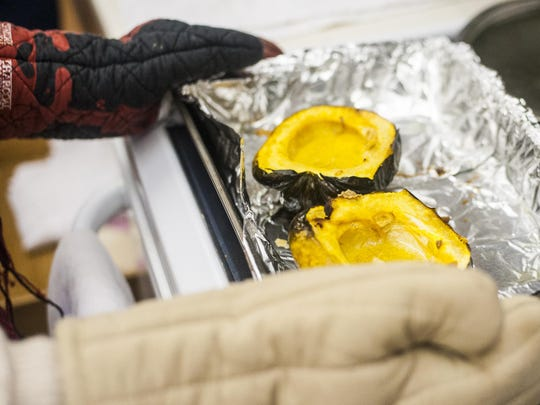 Abigail Lichliter takes acorn squash out of the oven