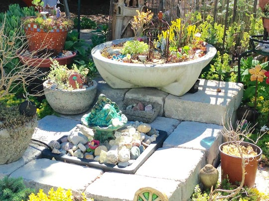 The tiny figures and plants in the fairy garden area