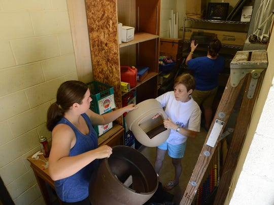 Jessica Gastelum, left, Joanne Magyari and Jennifer Latham work on clearing out closet space for the Parent Teacher Organization on July 22 at East Elementary School. Gastelum and Magyari's children attended Nova Elementary School last year but due to Vision 2020 their children will be attending East this year.