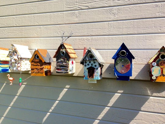 Seven charming birdhouses greet guests entering the