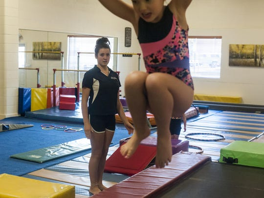 Angel Buhler, a junior at C.M. Russell High School, watches students do jumping drills at Great Falls Gymnastics Academy.