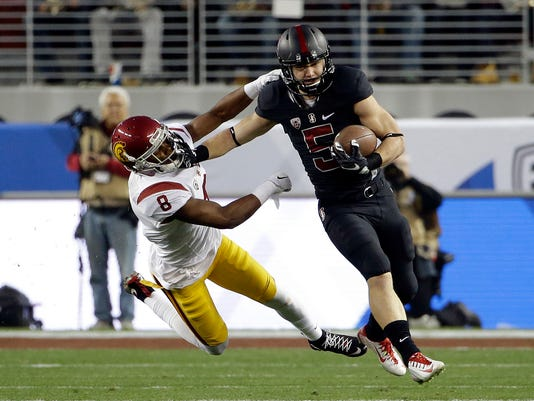 FILE - In this Dec. 6, 2015, file photo, Stanford running back Christian McCaffrey (5) stiff-arms Southern California's Iman Marshall on a kickoff return during the Pac-12 Conference championship NCAA college football game in Santa Clara, Calif. Stanford as a comfortable favorite against Southern California does not even seem weird anymore. These days it is more notable when the Trojans beat the Cardinal than the other way around. (AP Photo/Marcio Jose Sanchez, File)