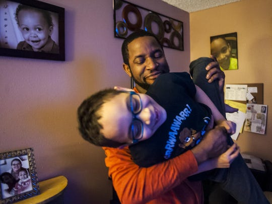 Trayson Harrell, 8, plays with his father, Eric, before his evening lessons. Eight years ago Trayson was diagnosed with sickle cell disease and the family hopes he will be classified as cured by June.