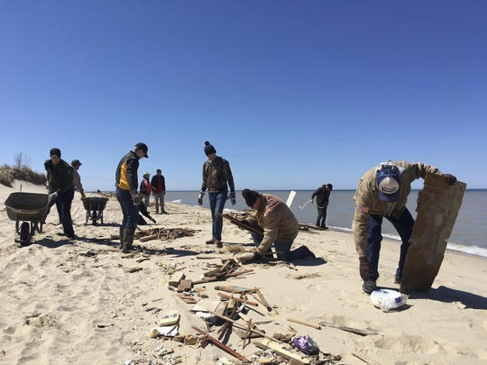 Caden Schmutzler and Ben Miller of Manistee, standing center, are among volunteers clearing debris from Ludington State Park beach.