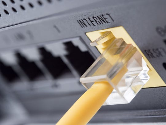 The back of a modem with a yellow ethernet cable plugged into it.