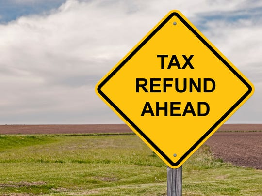 Diamond-shaped yellow road sign with the words tax refund ahead.