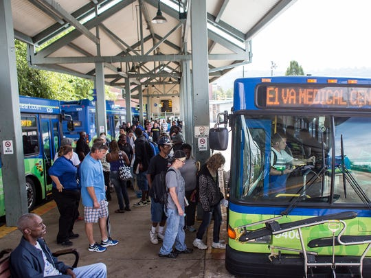 People board buses at the ART Station, or Asheville Transit Center, on Coxe Avenue in downtown Asheville in the summer.