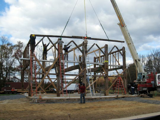 Workers erect the Dutch barn at the Rockingham Historic Site in Franklin, NJ.