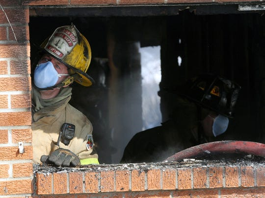 Marion City firefighters tear down interior studs still smoldering after taming a house fire at 808 Underwood on Monday morning, Mar. 2, 2015. The fire appeared to have started on a living room sofa. James Miller/The Marion Star