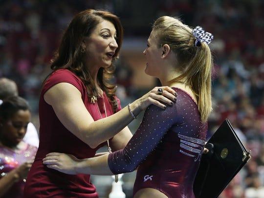 Alabama women's gymnastics coach Dana Duckworth celebrates with Lauren Beers after Beers scored a 9.90 on the balance beam during a gymnastics meet against Auburn on Friday, Feb. 6, 2015, in Tuscaloosa, Alabama.