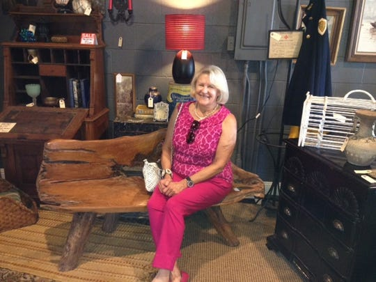 Christine Sowders, who was Ms. Cheap's guide for bargain shopping around Bowling Green, Ky., takes a seat on a handmade driftwood bench at Rummage 300.