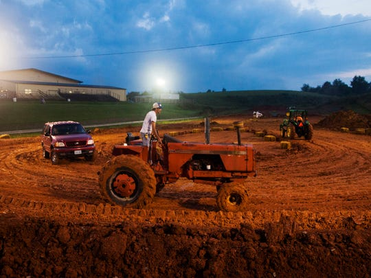 Jay Bodkin rounds a figure-eight track on his tractor at the Augusta County Fair before the start of the Redneck Rally race in Staunton on Aug. 5. A fleet of vehicles was tasked with trying to pack down the dirt track after the afternoon's rain washed it out.