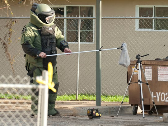 A bomb squad member removes explosive materials found in a Visalia apartment in December 2014.