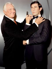 George Lazenby poses with his 007 wax figure at Madame