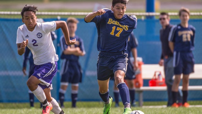 Battle Creek Central's Cesar Duran (17) advances the ball while Lakeview's Lal Lian follows (2) during the 2015 All-City Soccer Final.