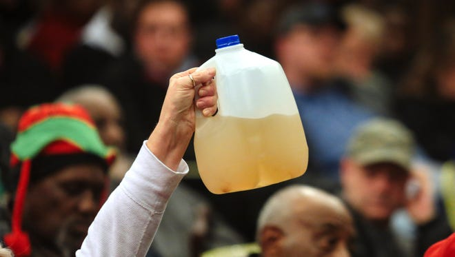 Flint resident Gladyes Williamson-Bunnell holds a sample of water that came from her home she saved from August 2014 after Flint switched from getting it's water from Detroit to using the Flint River water as a drinking source while officials spoke to a crowd about the water quality issues at a town hall meeting in the Flint City Hall dome on Jan. 21, 2015.