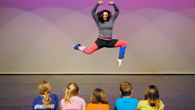 Brittini Cleland performs a dance move for Sartell students during Wednesday's Math SmARTs activities.