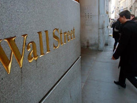 In this Oct. 2, 2014 file photo, Wall Street is etched in the facade of a building in New York's Financial District. U.S. and global stocks fell Tuesday as investors closed their positions ahead of the New Year and amid concern over political uncertainty i