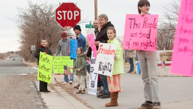 Residents of Colorado City, Ariz. rally in support of the U.S. Justice Department and the government's lawsuit against the city Saturday, Jan. 23, 2016. Jurors found that the city discriminates against its residents last year, and the federal judge presiding over the case issued a ruling Tuesday ordering Colorado CIty and its Utah twin, Hildale, to establish a monitor to help ensure city officers uphold the U.S. Constitution.