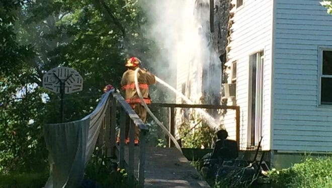 Firefighters battle a blaze at a house near the intersection of Brown County P and Van Lanen Road in the town of Green Bay on Wednesday morning.