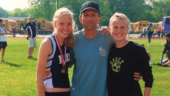 Essex coach Joe Gonillo, center, poses with Alexis Purdy, left, and Leah Murdoch during a high school track and field meet.