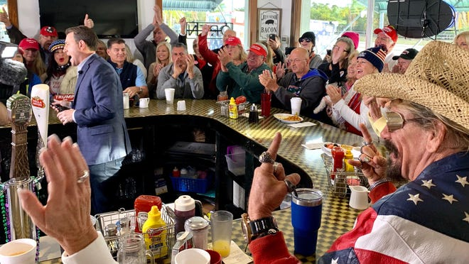 Fans clap and shout while Fox News correspondent Todd Piro talks behind the counter at the Lighthouse Diner in Jupiter on Wednesday.