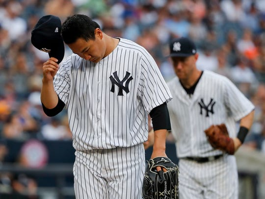Yankees starting pitcher Masahiro Tanaka walks off